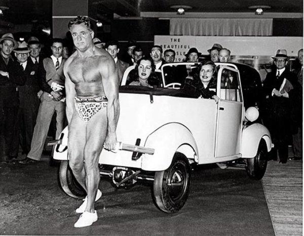 Чарльз Атлас выполняет силовой трюк по поднятию автомобиля