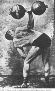 Джон Смит выкручивает гантель весом 84 кг (185 фунтов)